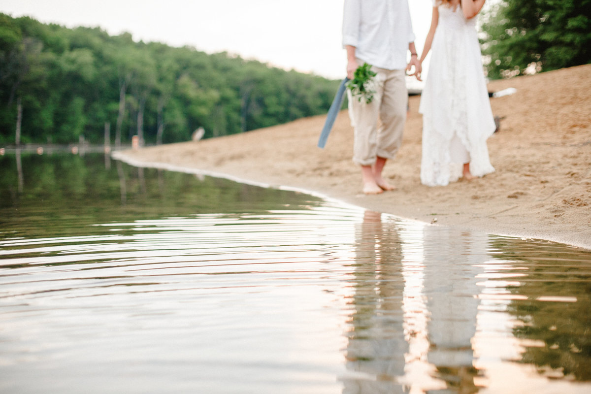 couple walks hand in hand over sand shore casual wedding photography and chester woods regional park rochester minnesota