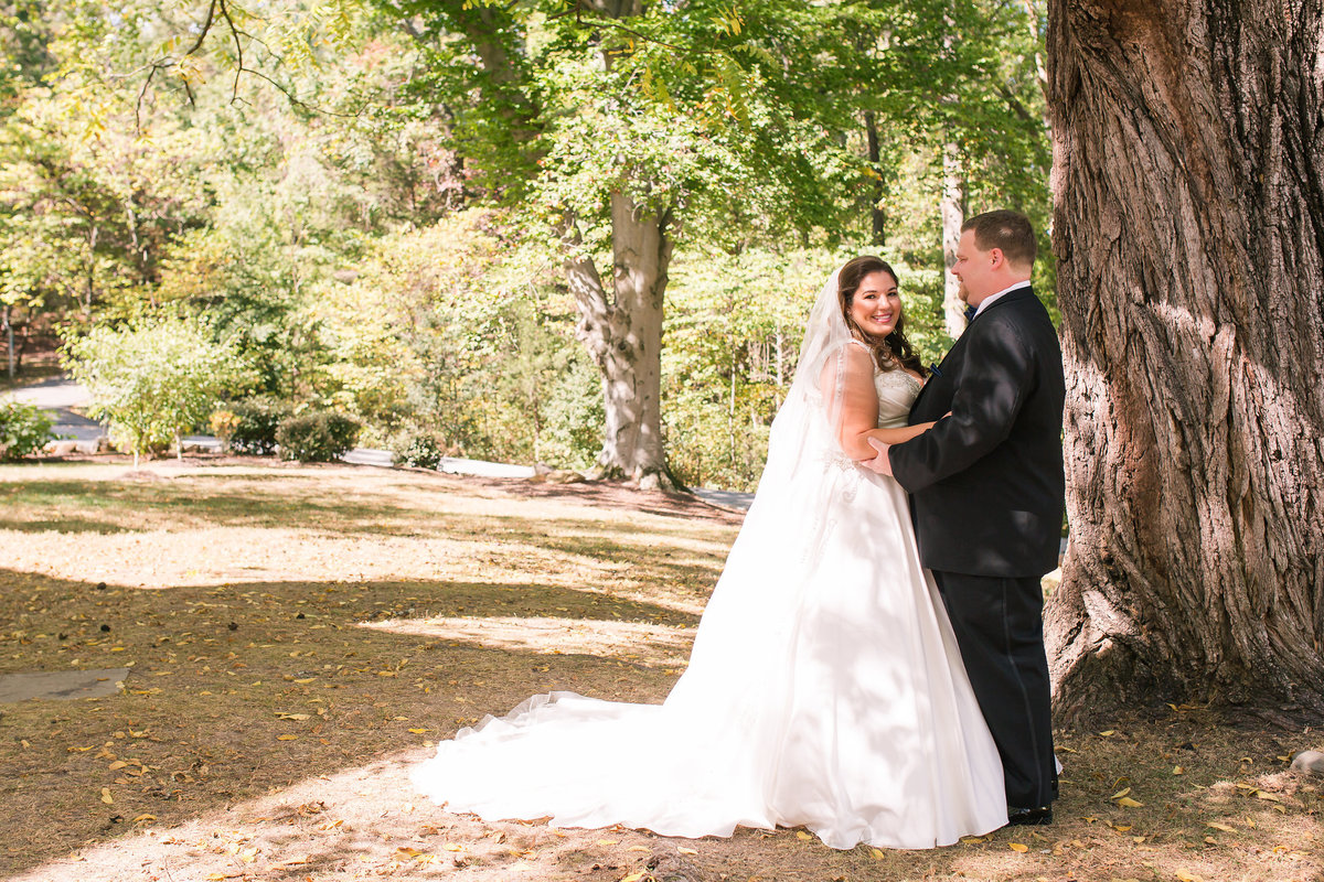 Bride and groom under a historic tree at Braehead Manor in Fredericksburg