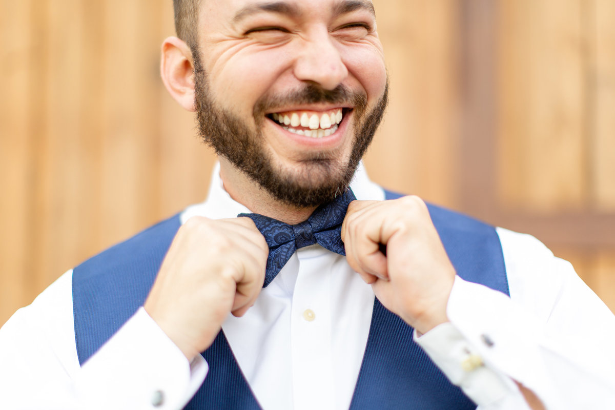 Groom smiles as he gets ready for their wedding day in Lakeland, Florida by adjusting his blue bow tie