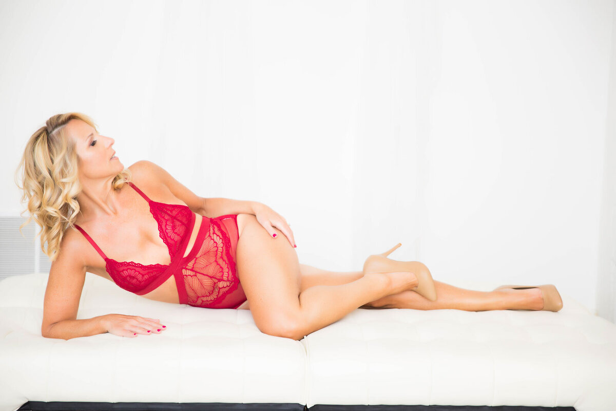 Blonde-women-in-red-lingerie-laying-down-with-leg-up-in-a-brightly-lit-room