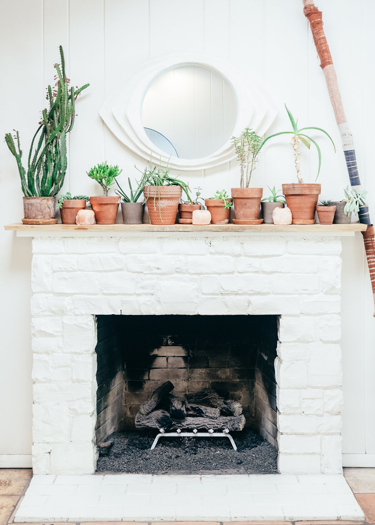 A white brick fireplace has a wooden mantlepiece covered in terracotta pots with plants.