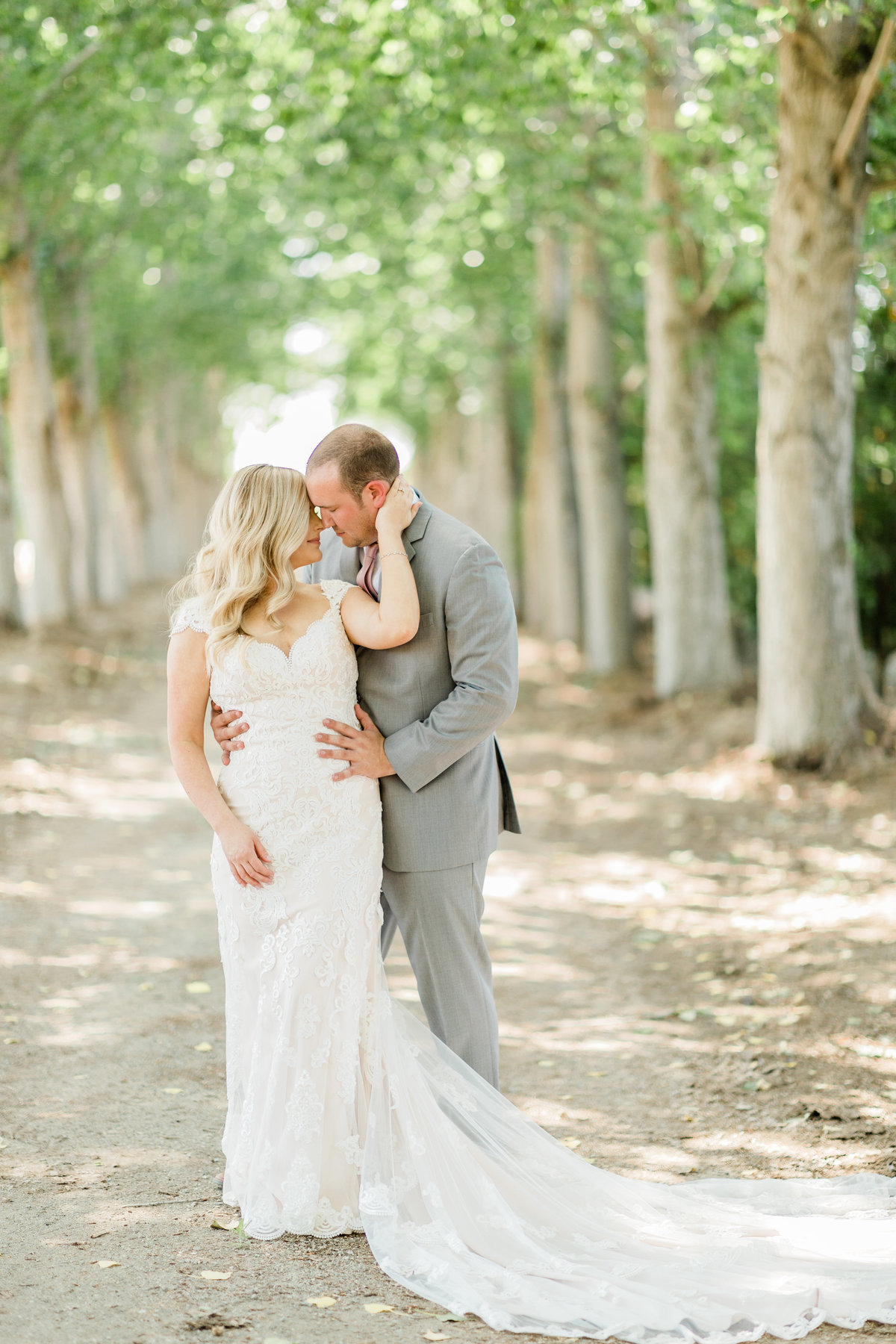 bride and groom embracing down the famous driveway of historic seven sycamores ranch in ivanhoe california