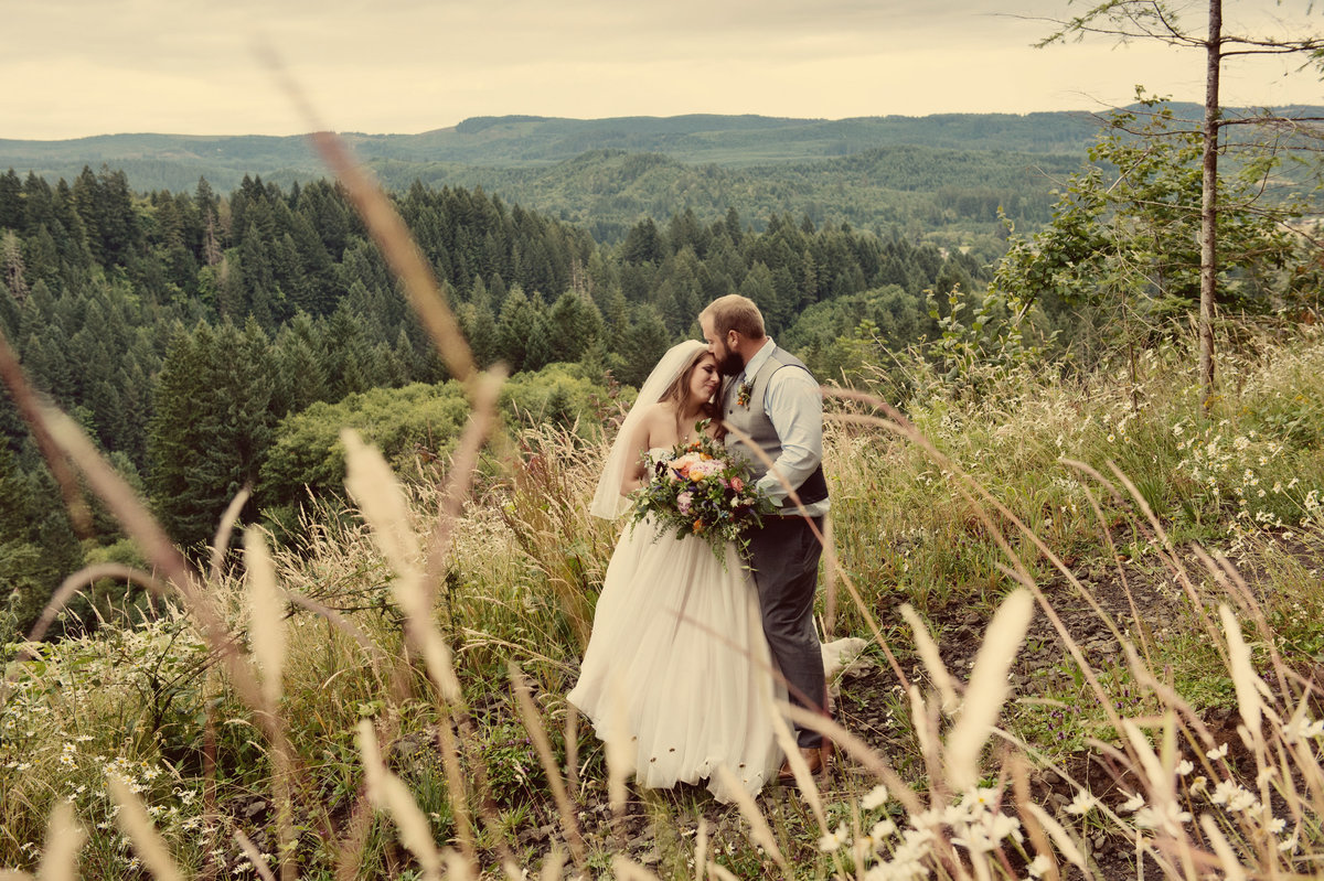 wedding couple pose on mountain in banks or