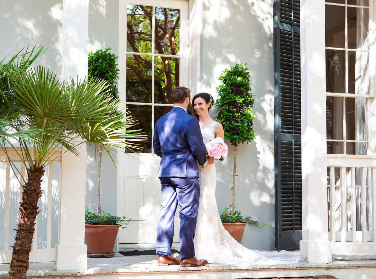 nola bride smiles at groom on the porch of The Terrell House