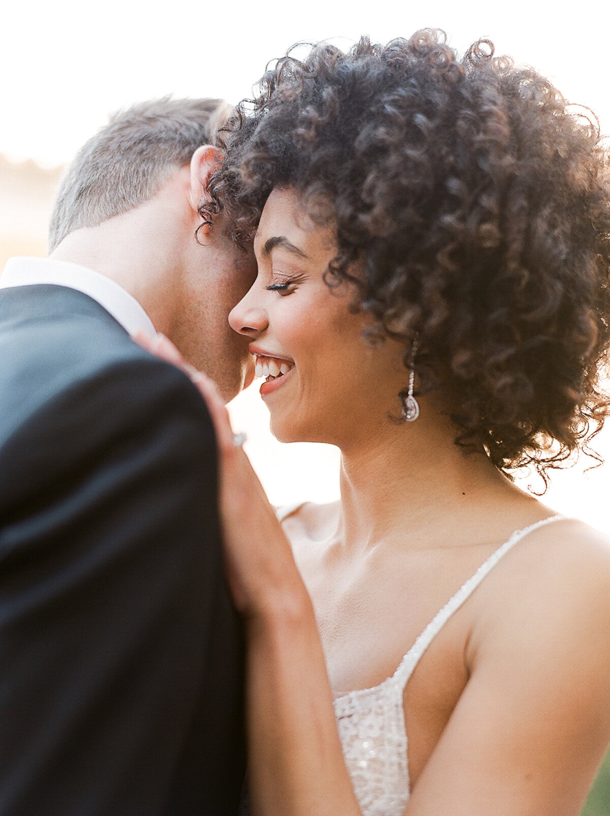 Bride and groom embracing and laughing at destination wedding