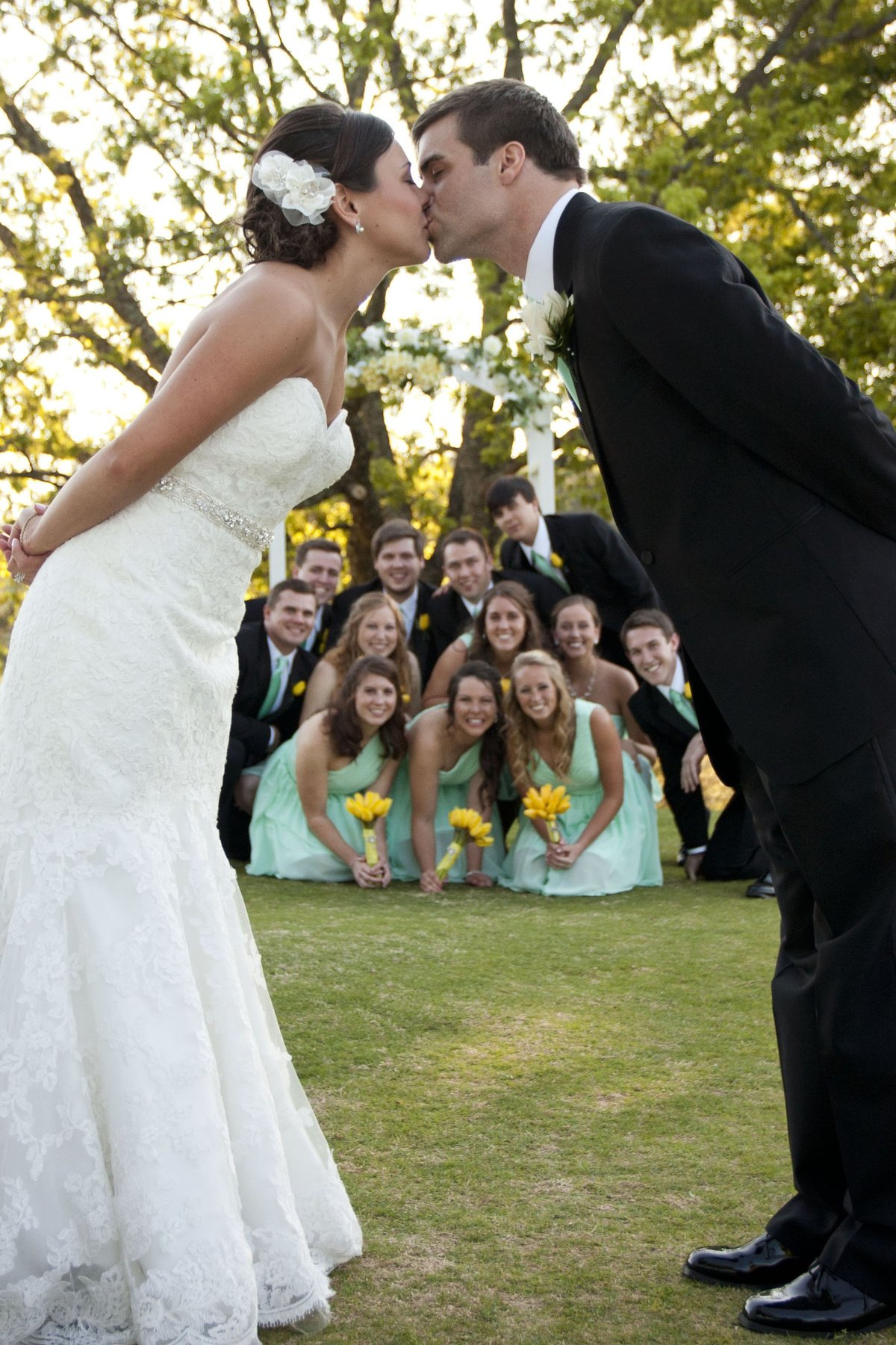 bride and groom kissing with bridal party in the background