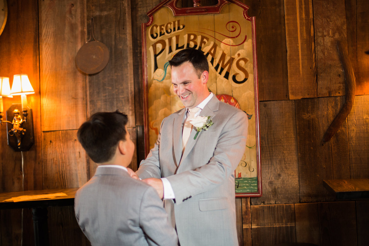 Groom helps son with suit prior to  1880 Union Hotel Wedding