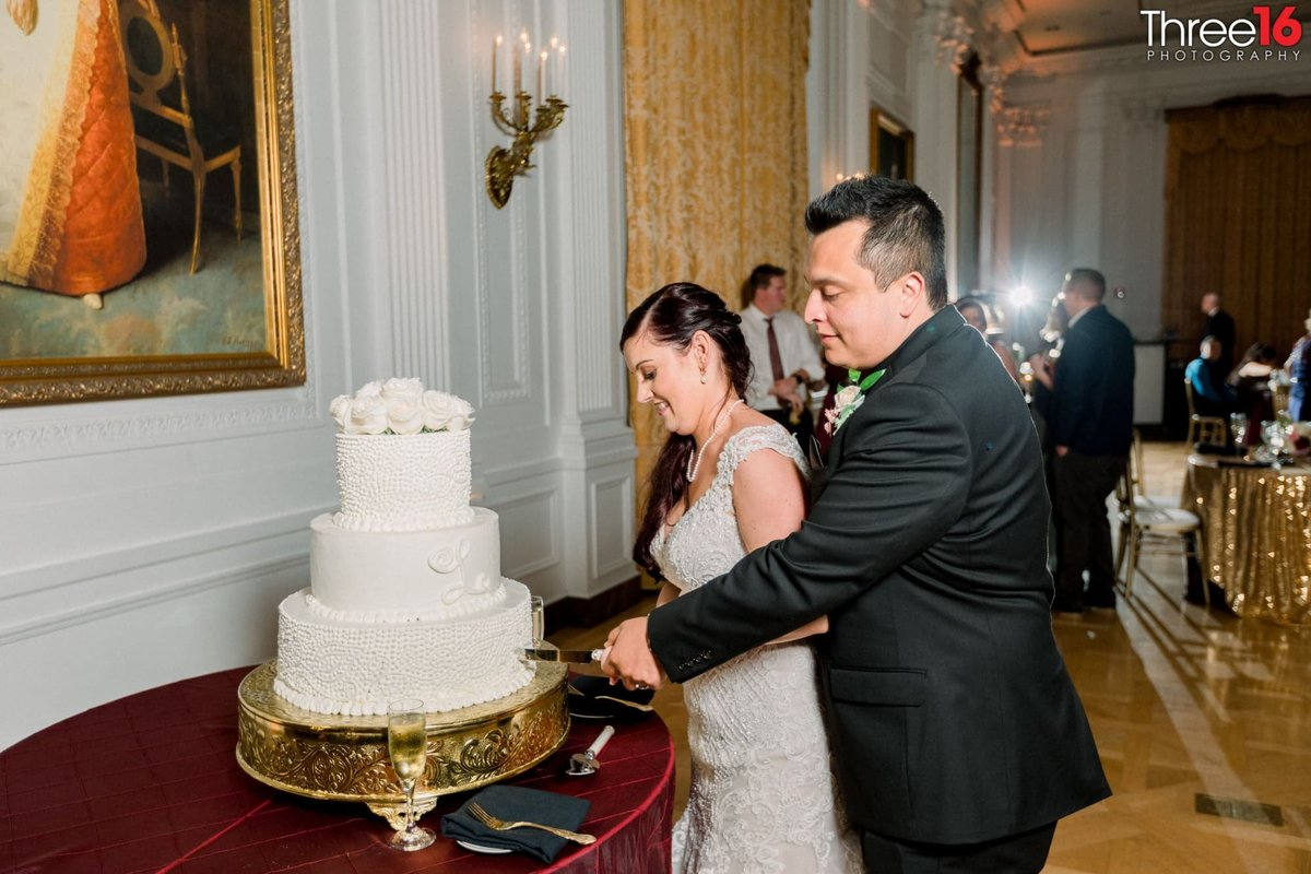 Bride and Groom cut into 3-tiered white wedding cake
