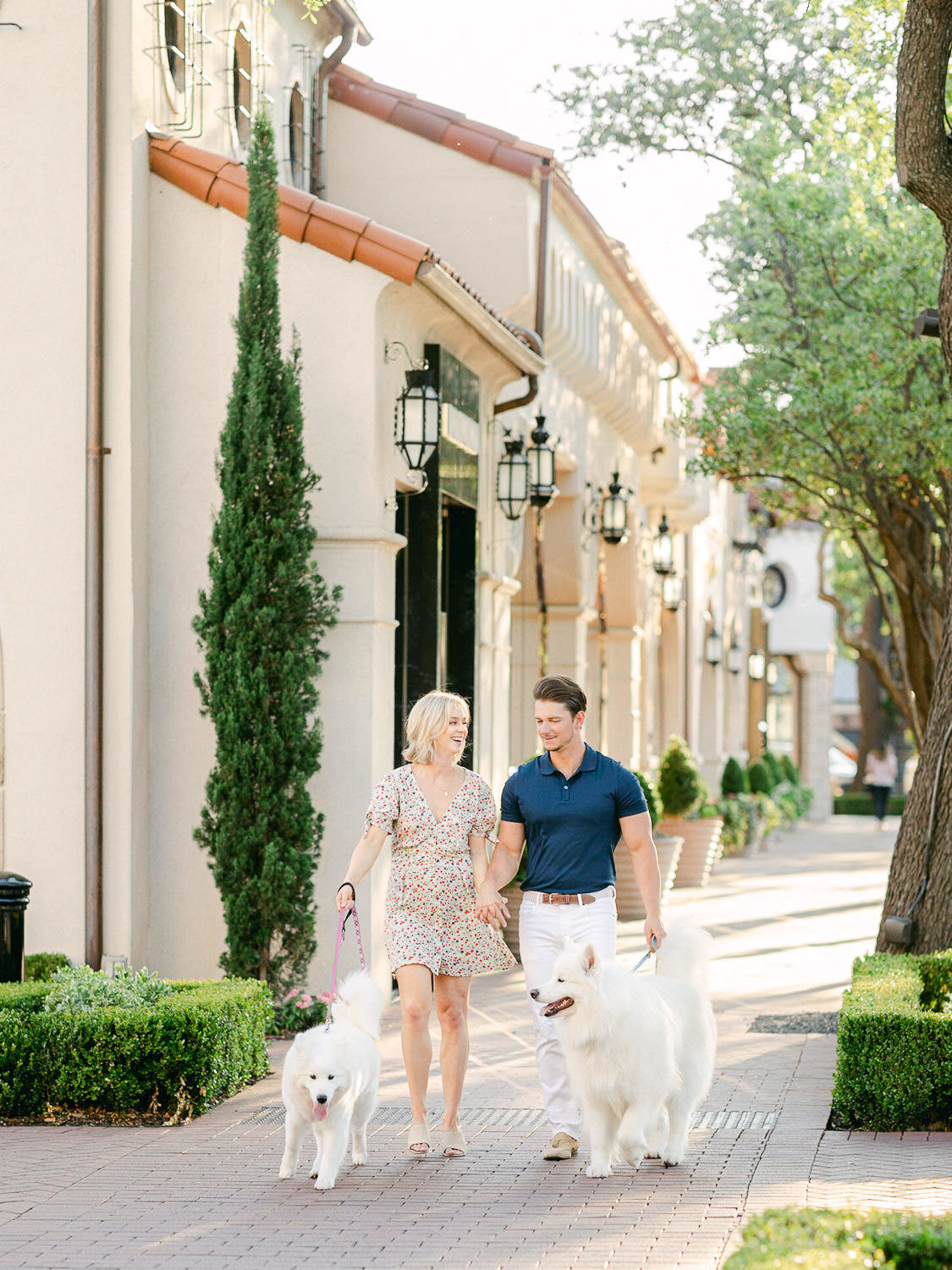 boy and girl holding hands and walking two large white dogs down sidewalk in Dallas