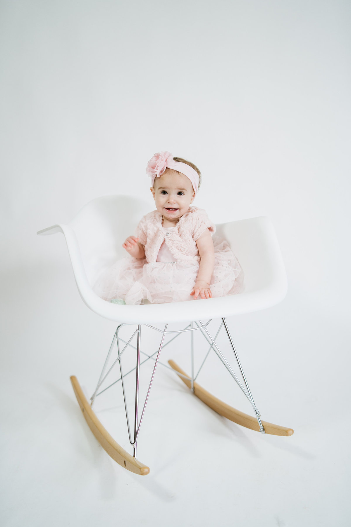 Baby toddler sitting in Eames rocking chair wearing pink dress in San Antonio photo studio on a white background
