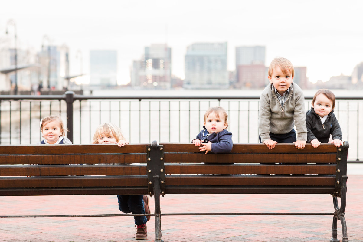 five children sitting on a bench peeking over the edge