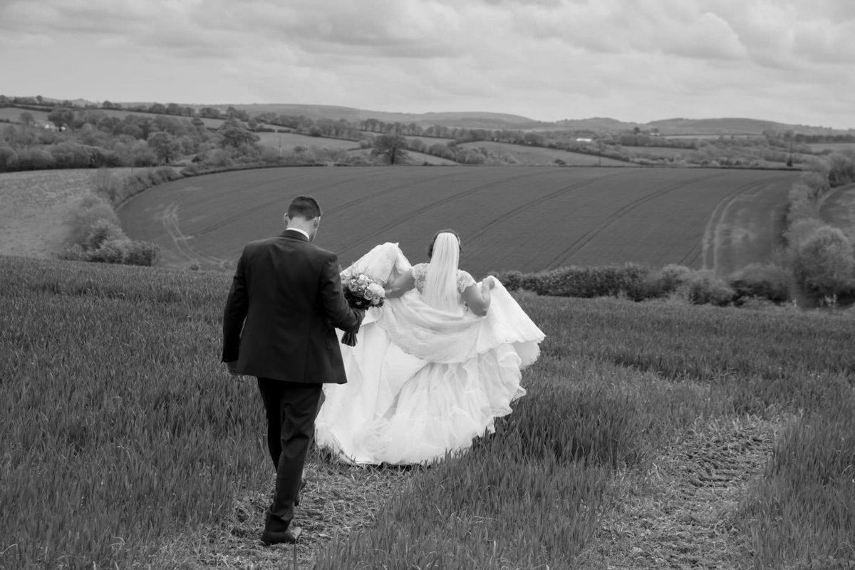 Black and white wedding couple in field at The Oak Barn Devon