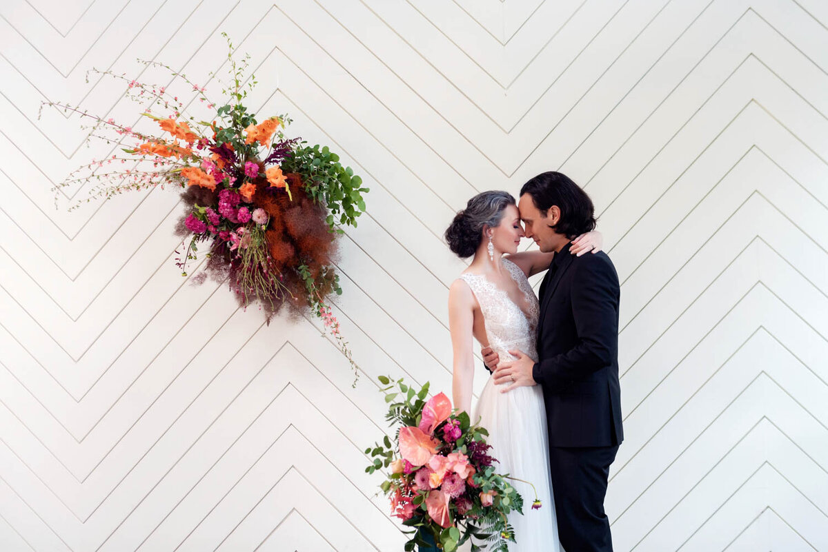 a bride and groom hug in front of a white herringbone wall with big colorful flowers