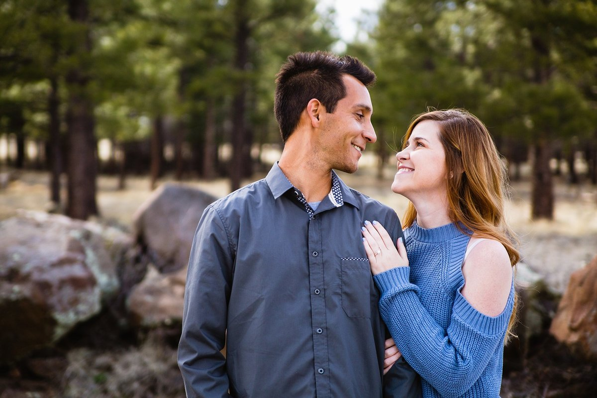 Couple happily looking at each other during their Flagstaff, AZ engagement session by PMA Photography.