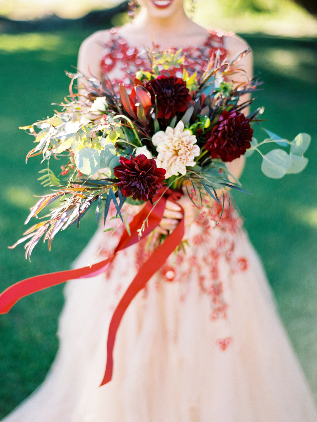 red and blush wedding dress and red bouquet