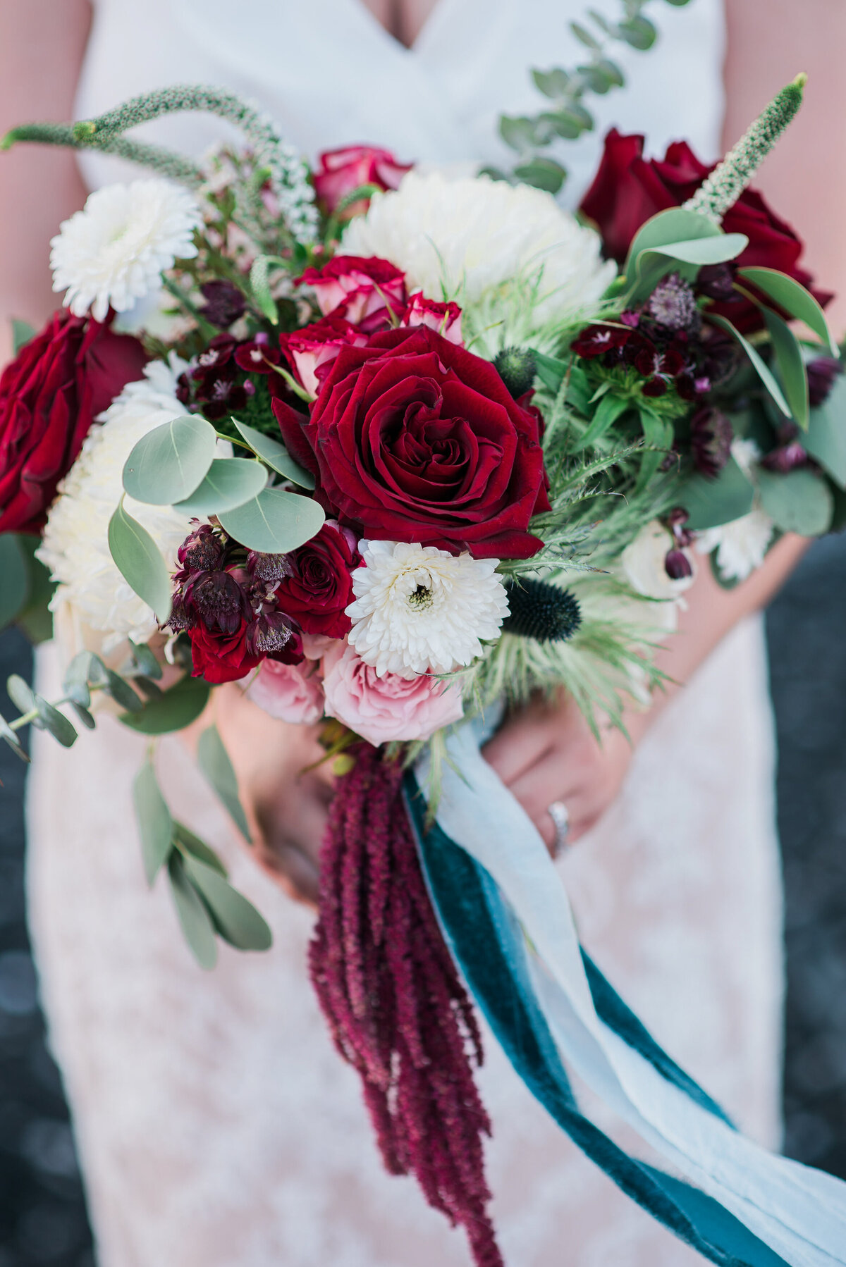 bridal bouquet with red roses and blue ribbon