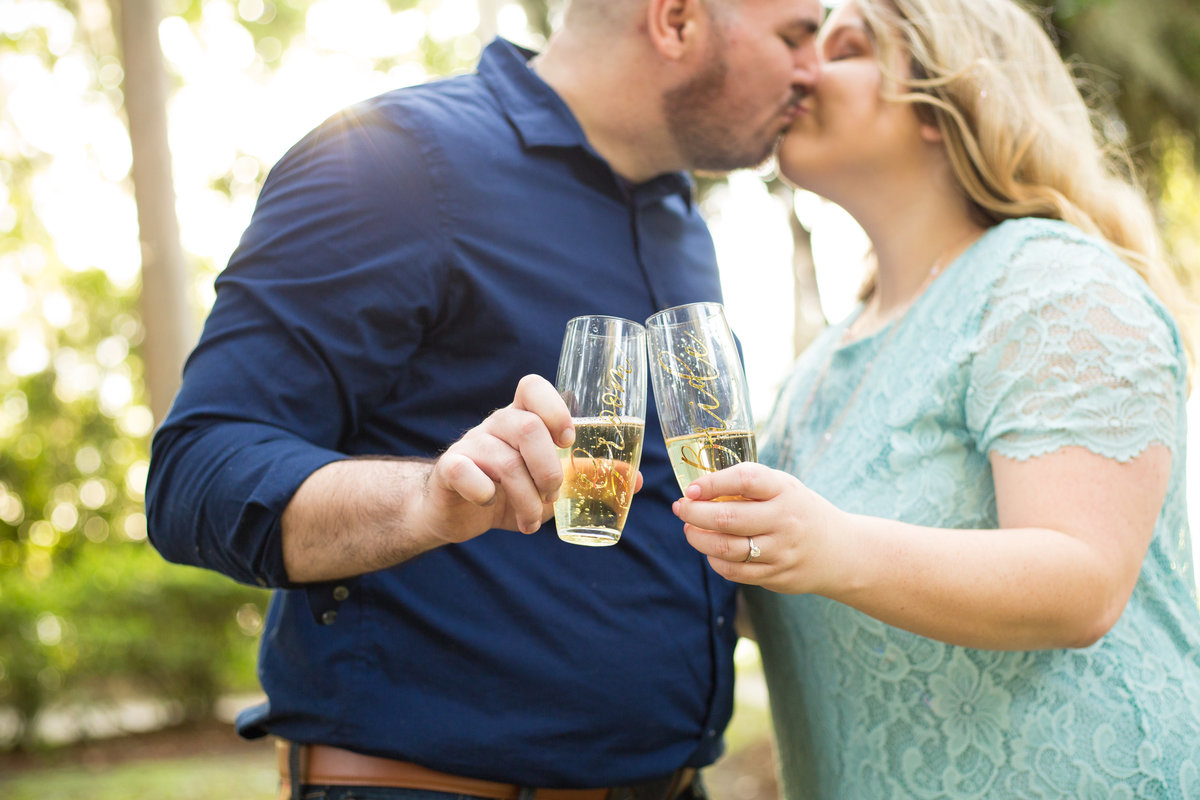Couple cheers with Mr. and Mrs. glasses at their engagement photoshoot in Orlando, Florida
