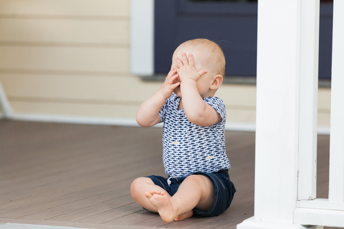CT family photographer captures a baby playing peek-a-boo on the front steps of his Milford home