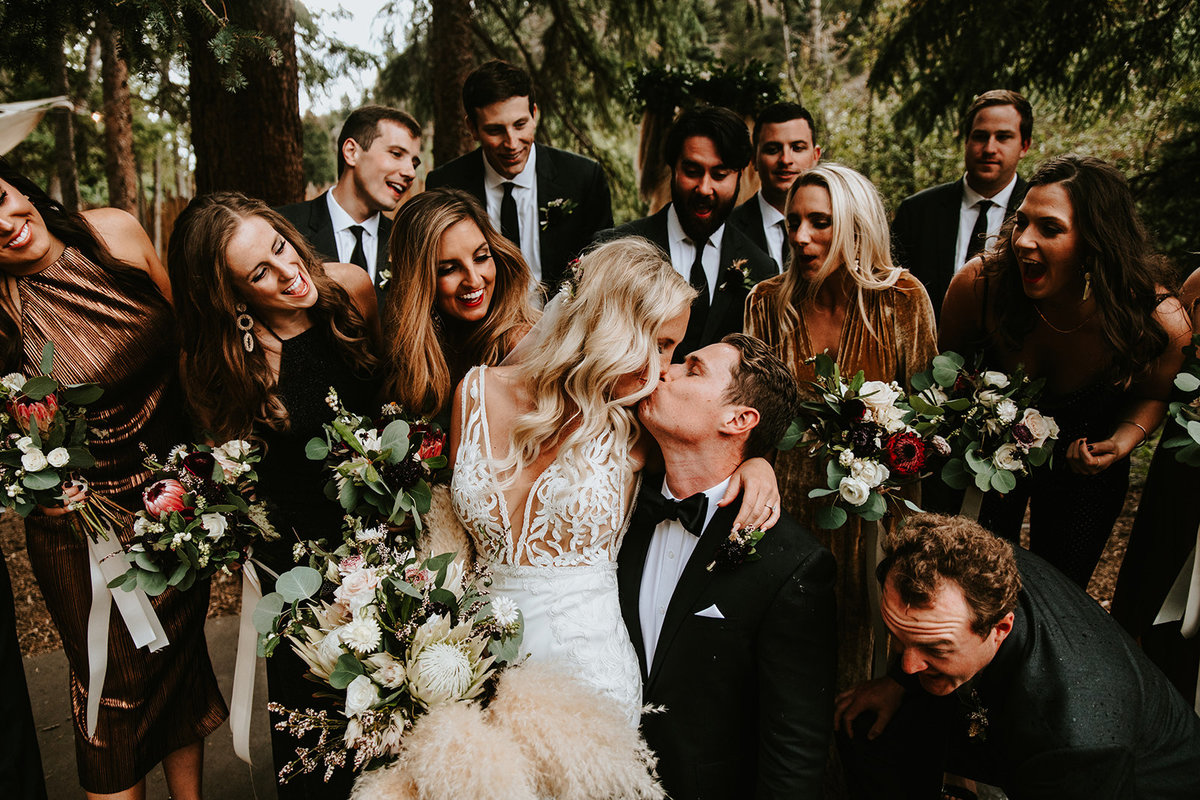 kiss surrounded by bridal party at the Blackstone Rivers Ranch in Idaho Springs, CO