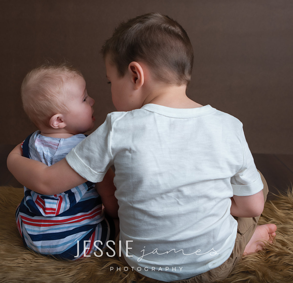a toddler boy and baby brother sharing a secret