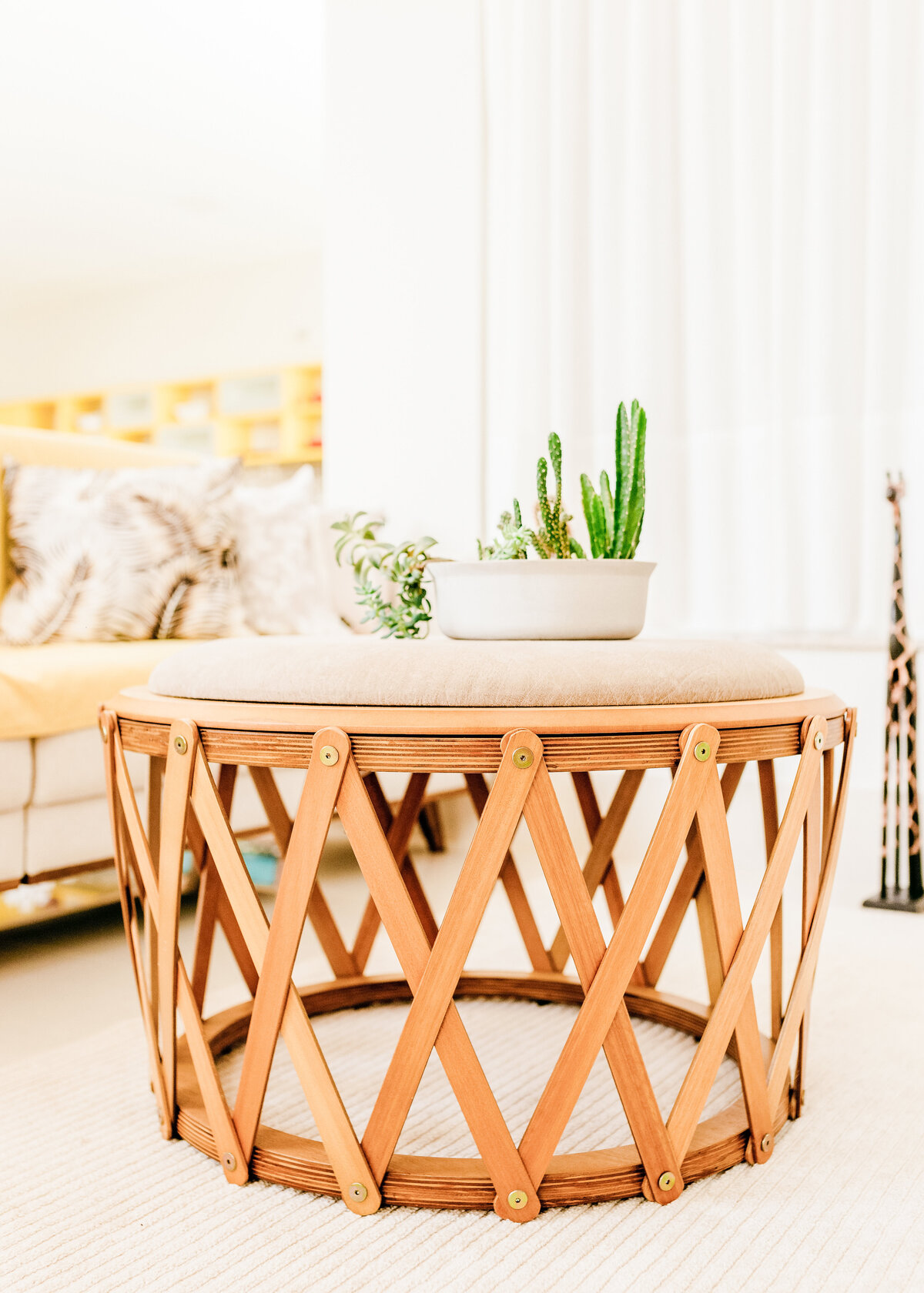 A hollow round wooden coffee table drum is on a white rug in a light lounge.