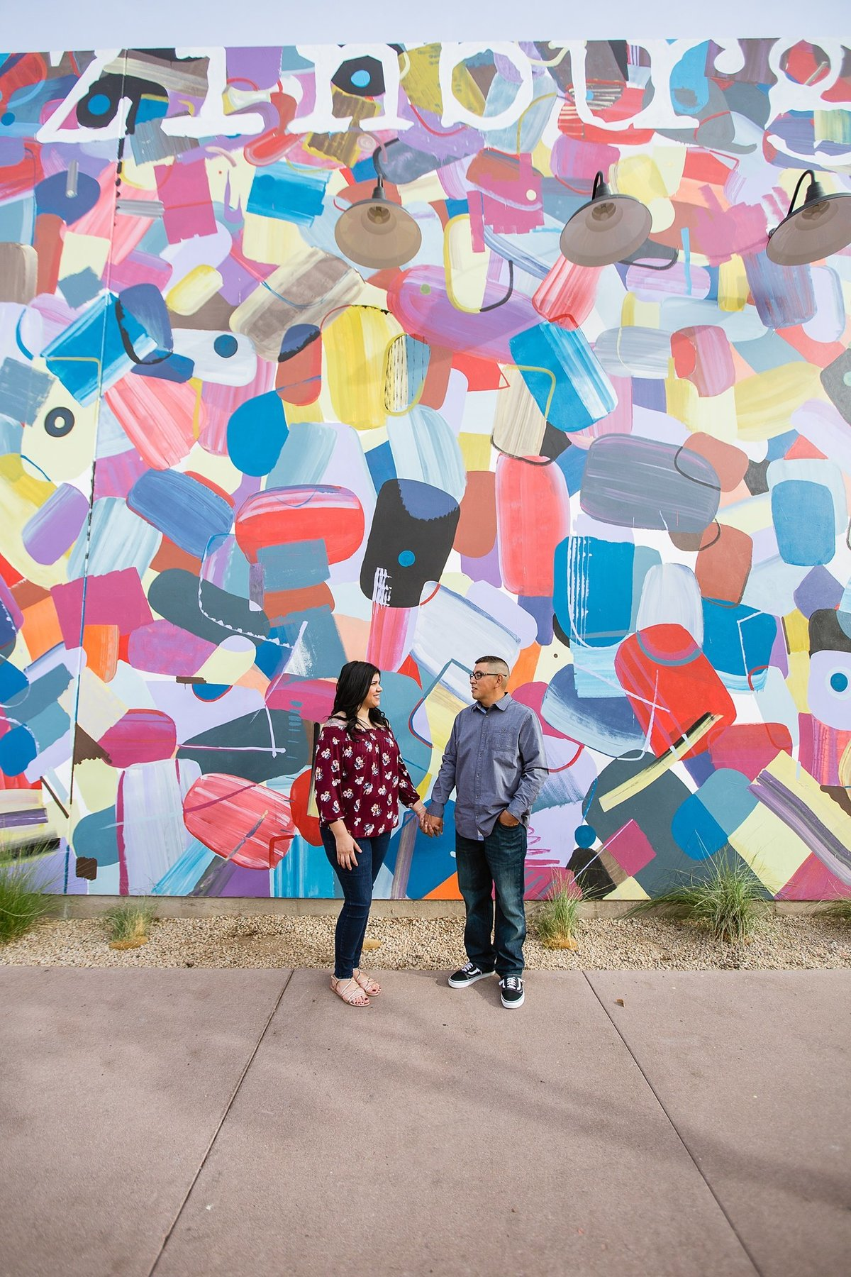 Couple looking at each other in front of a colorful art mural in downtown Gilbert by engagement photographer PMA Photography.