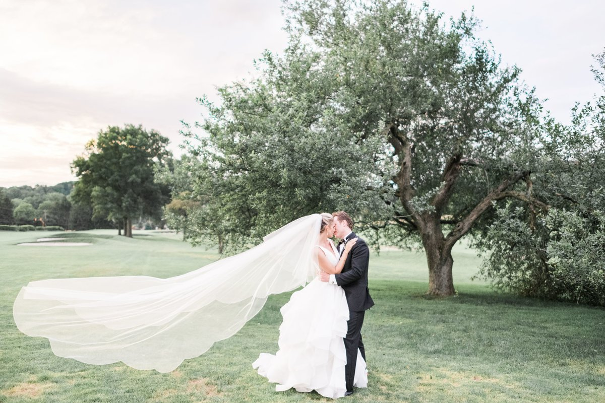 Bridge and groom with long veil in a field first look