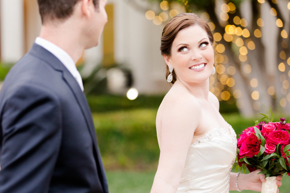 Bride smiles as she looks back at her groom during their bridal portraits at villa de amore by matty fran photography