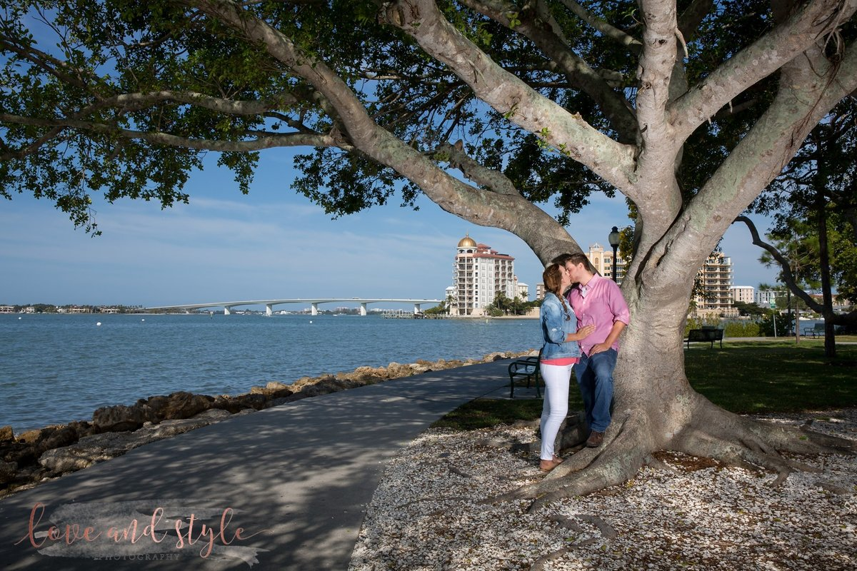 Sarasota Engagement Photography of couple  kissing under a tree at  Bayfront Park