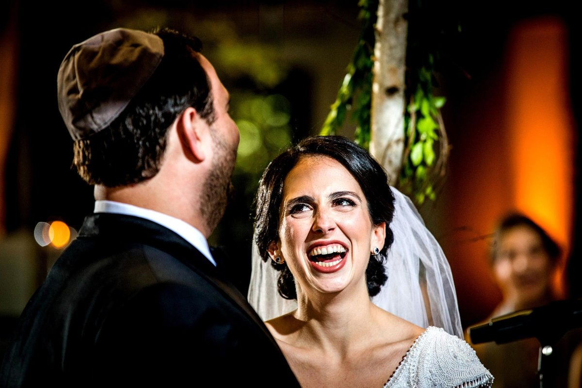 A bride laughs with her groom at a Harold Washington Library wedding ceremony.