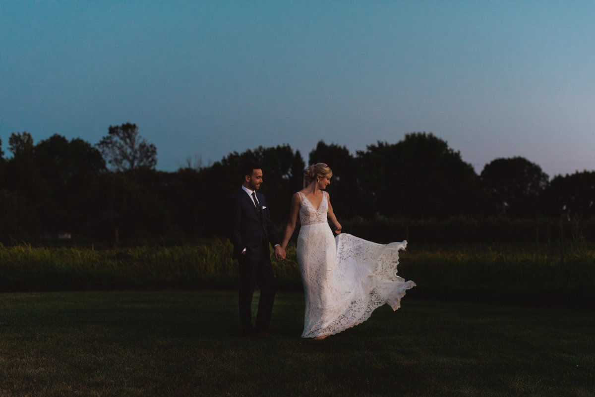 Bride and groom at sunset in a field