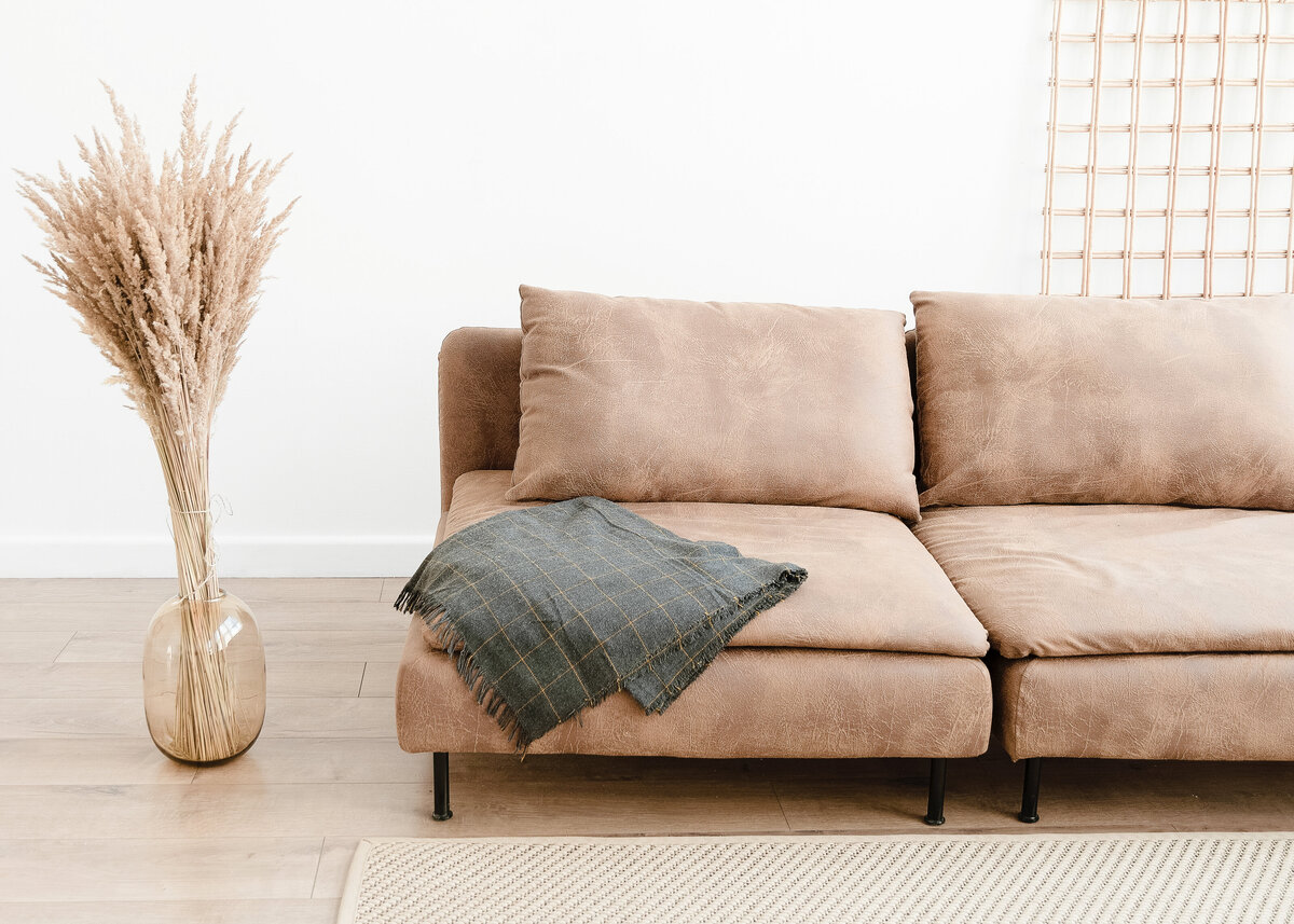 A tan leather sofa is next to glass vase of pampas grass in a modern interior design.