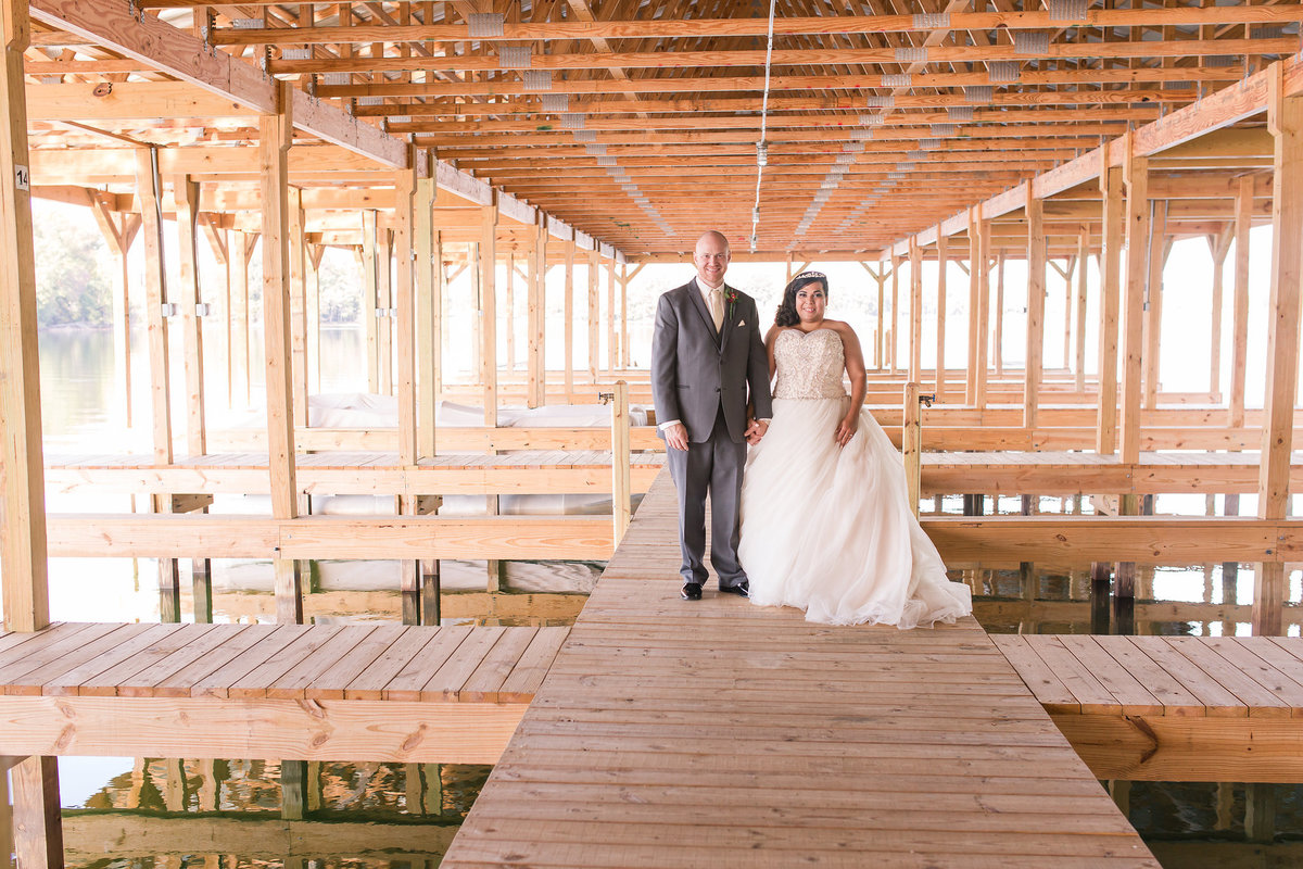 A bride and groom pose in a boat house at Lake Anna