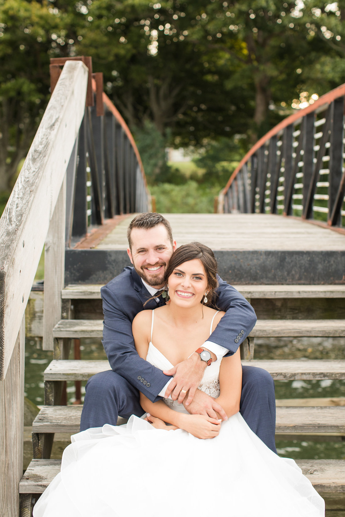 Jaimie + Josh sit on the bridge at Glen Manor House to get a photo