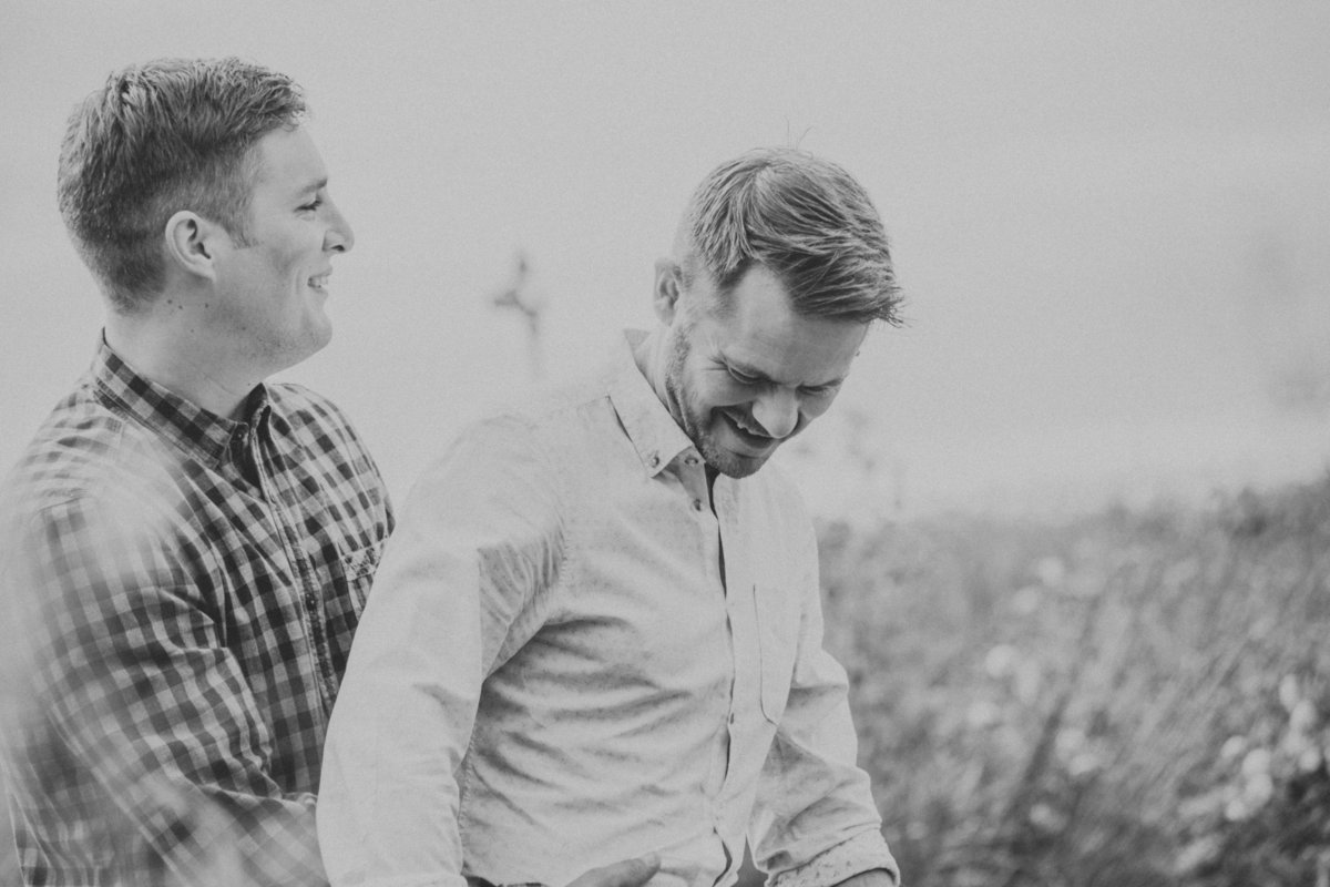 Gay couple on a pre-wedding engagement shoot hugging in a filed of grass by L:ancashire Wedding Photographer Jono Symonds