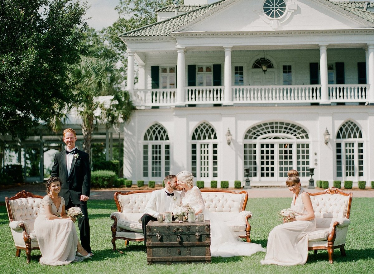 A vintage trunk and lounge set with a wedding party outside.