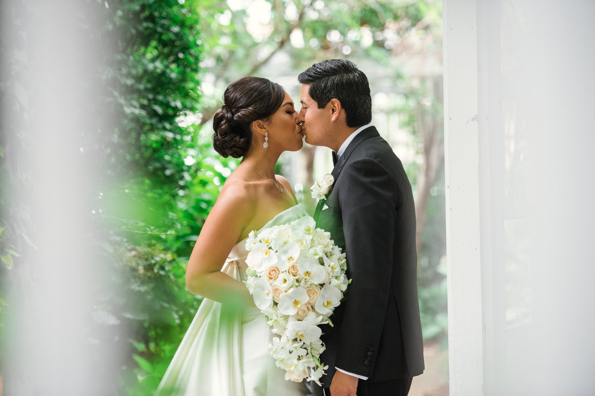 photo of bride and groom kissing outdoors from wedding at The Garden City Hotel