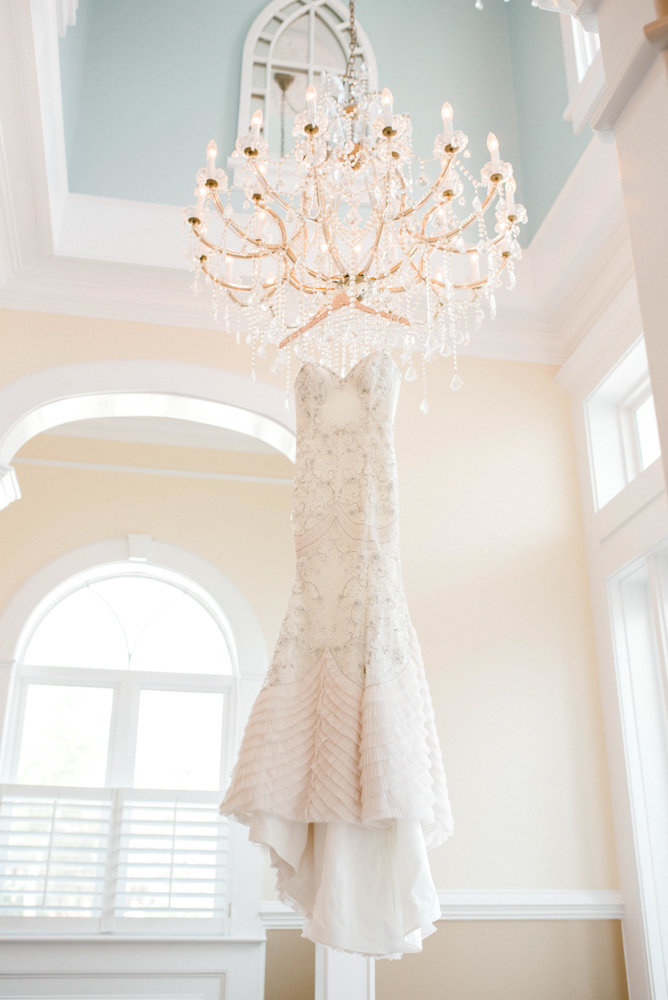 Bridal gown hanging from chandelier at Tybee Wedding Chapel
