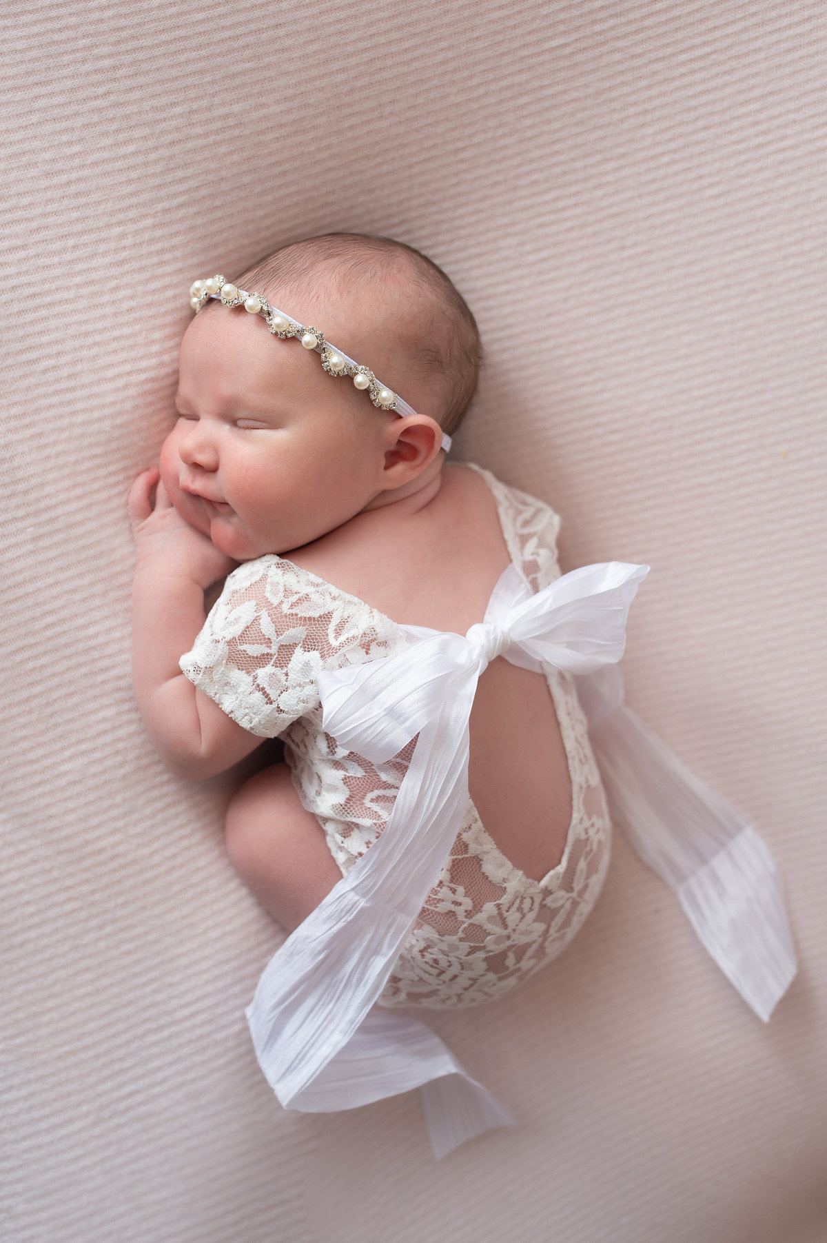 studio newborn session with baby girl in lace romper and headband