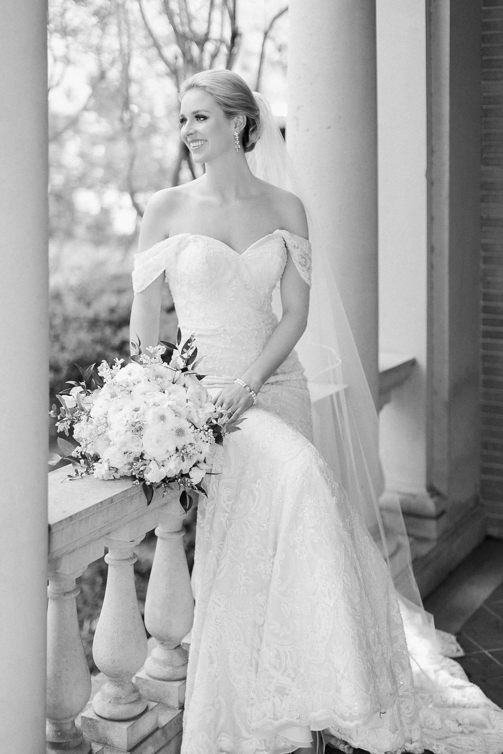 Bride sitting with bouquet in concrete porch columns smiling black and white