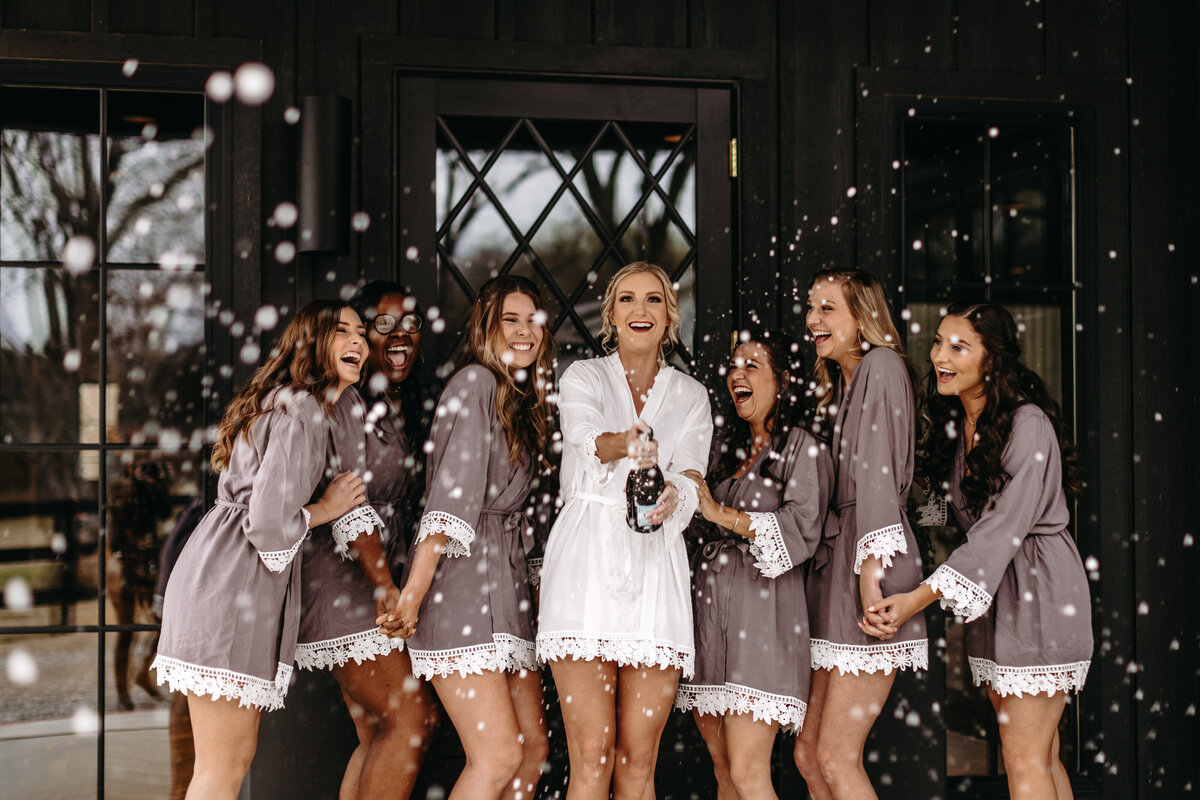 Bride popping champagne with her bridesmaids while getting ready for the wedding day