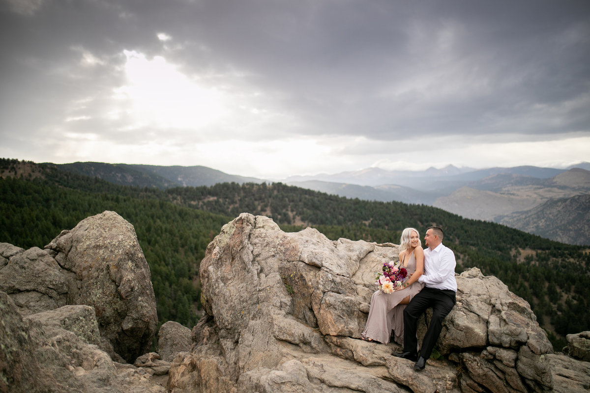 Engaged couple sitting on rocks during their mountain engagement session in Colorado