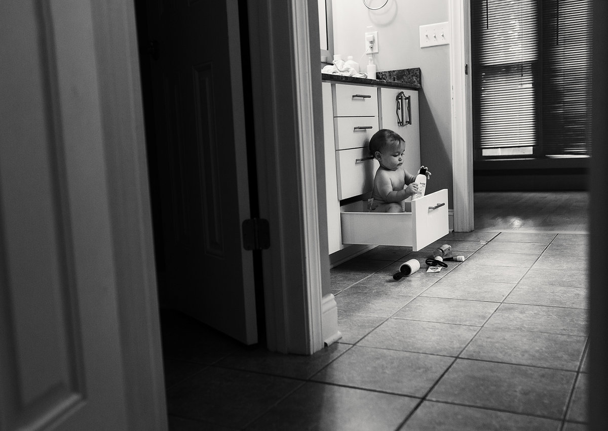 charlotte documentary photographer jamie lucido captures a candid image of a toddler sitting in a bathroom drawer