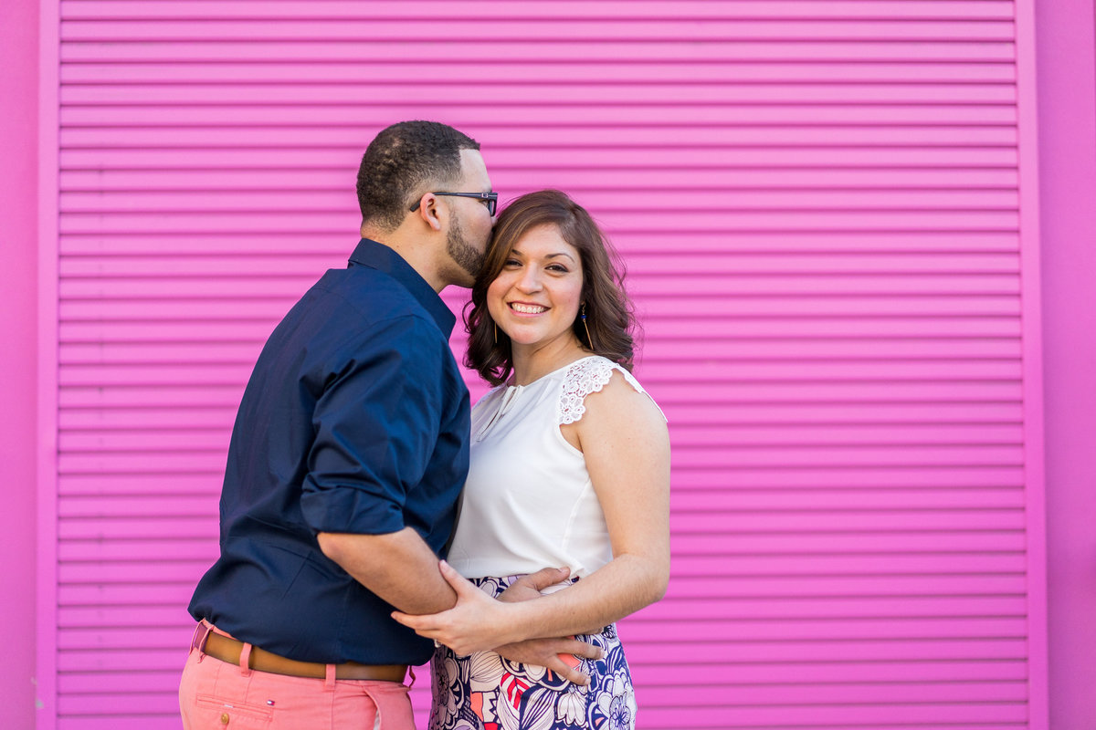 Engaged couple in front of pink wall at Market Square San Antonio