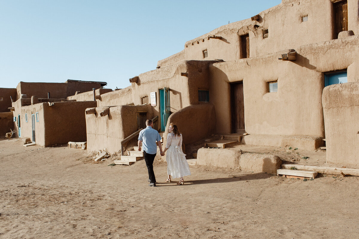 A married couple holds hands as they walk down the adobe house-lined streets of Taos