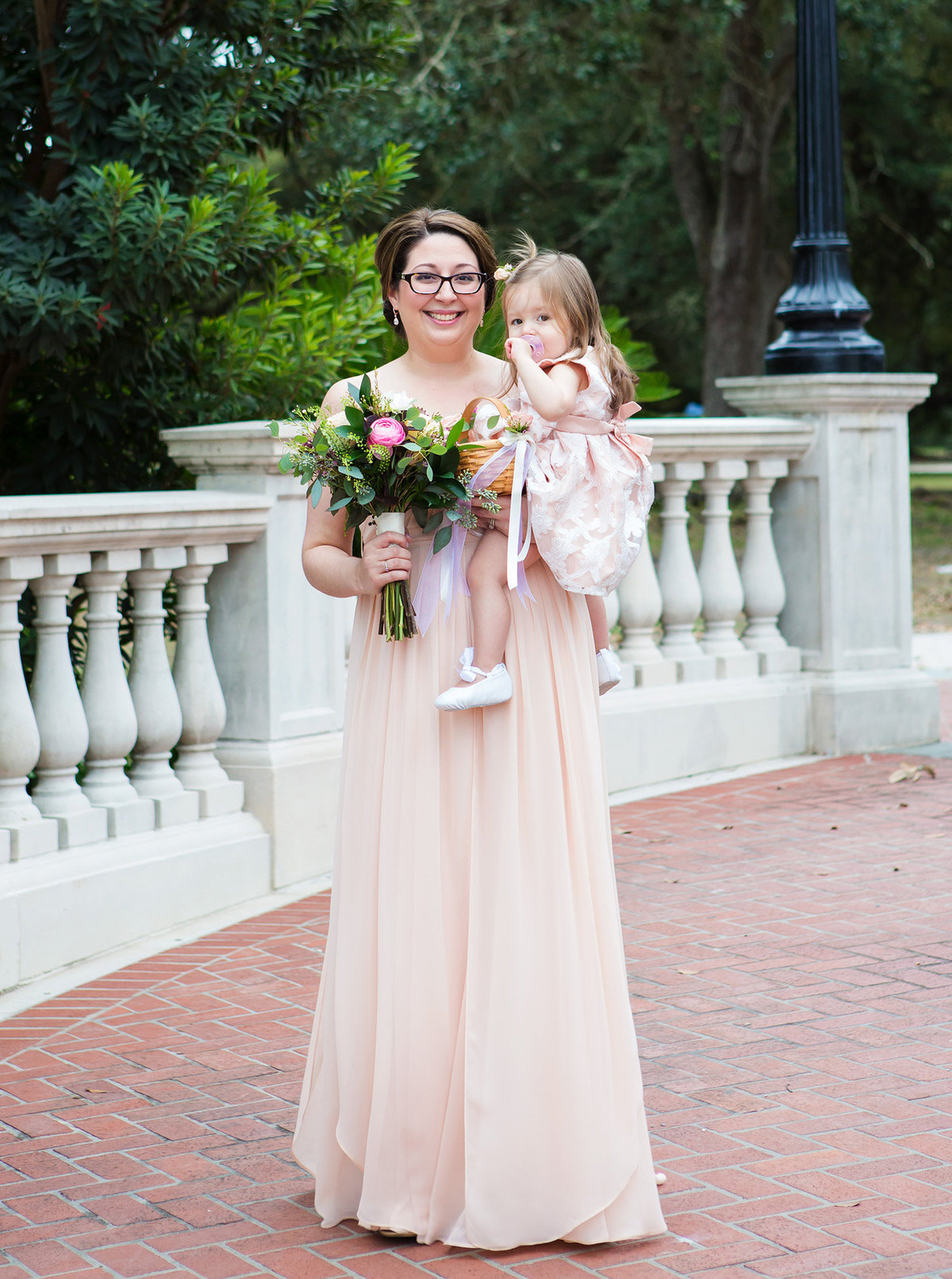NOLA bridesmaid with daughter walking down the cement pathway to wedding ceremony in Audubon Park