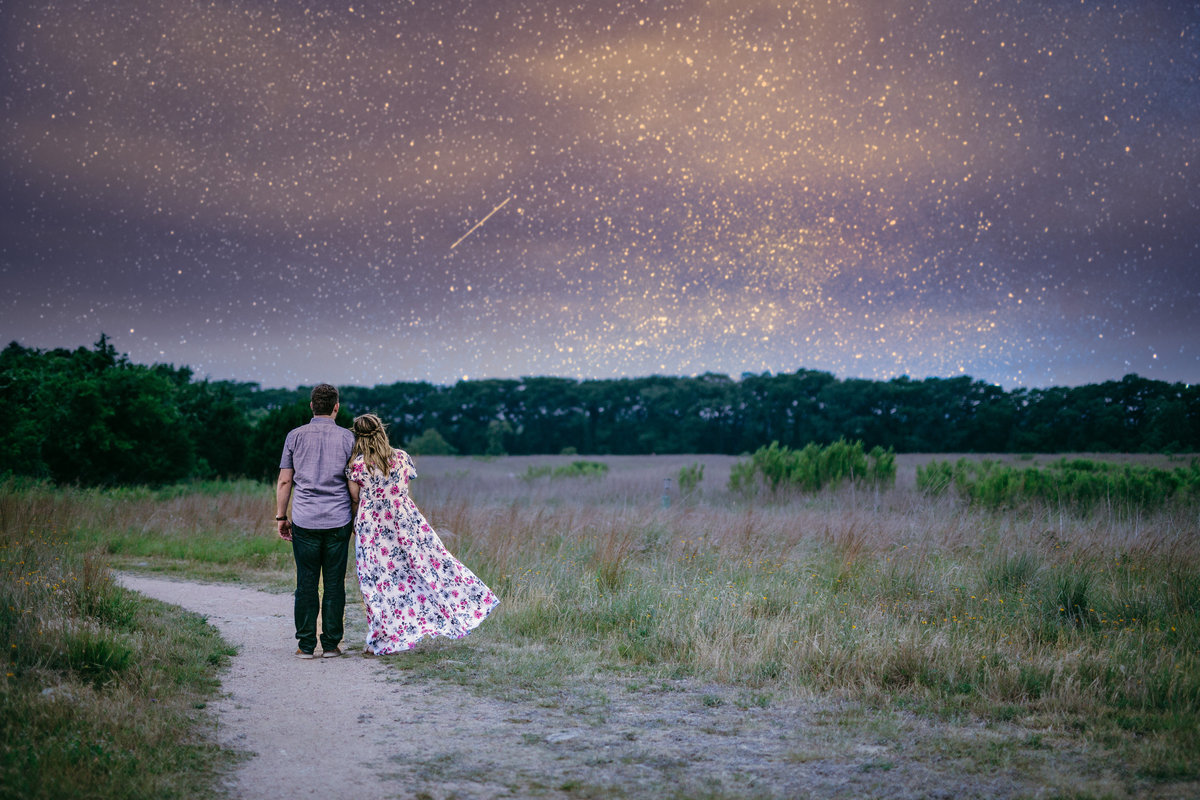 Engaged couple staring off into the distance at a starry night sky while standing in an open field in Boerne, Texas