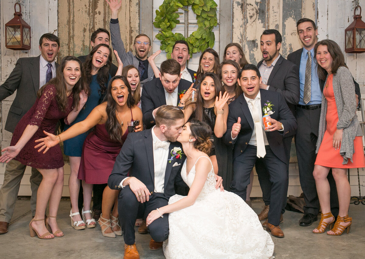 A fun bridal party photo. The bride and groom are kissing while their guests cheer behind them