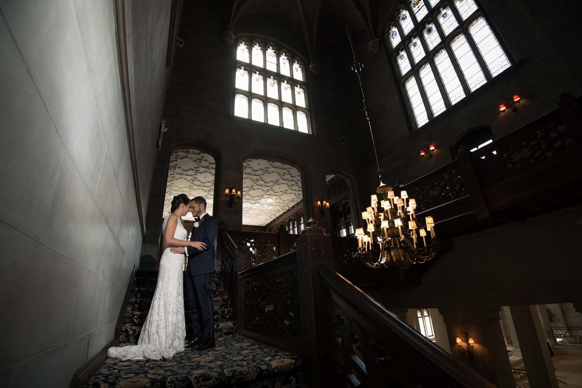 Bride and groom in each other's arms at the top of the stairs at Hempstead House