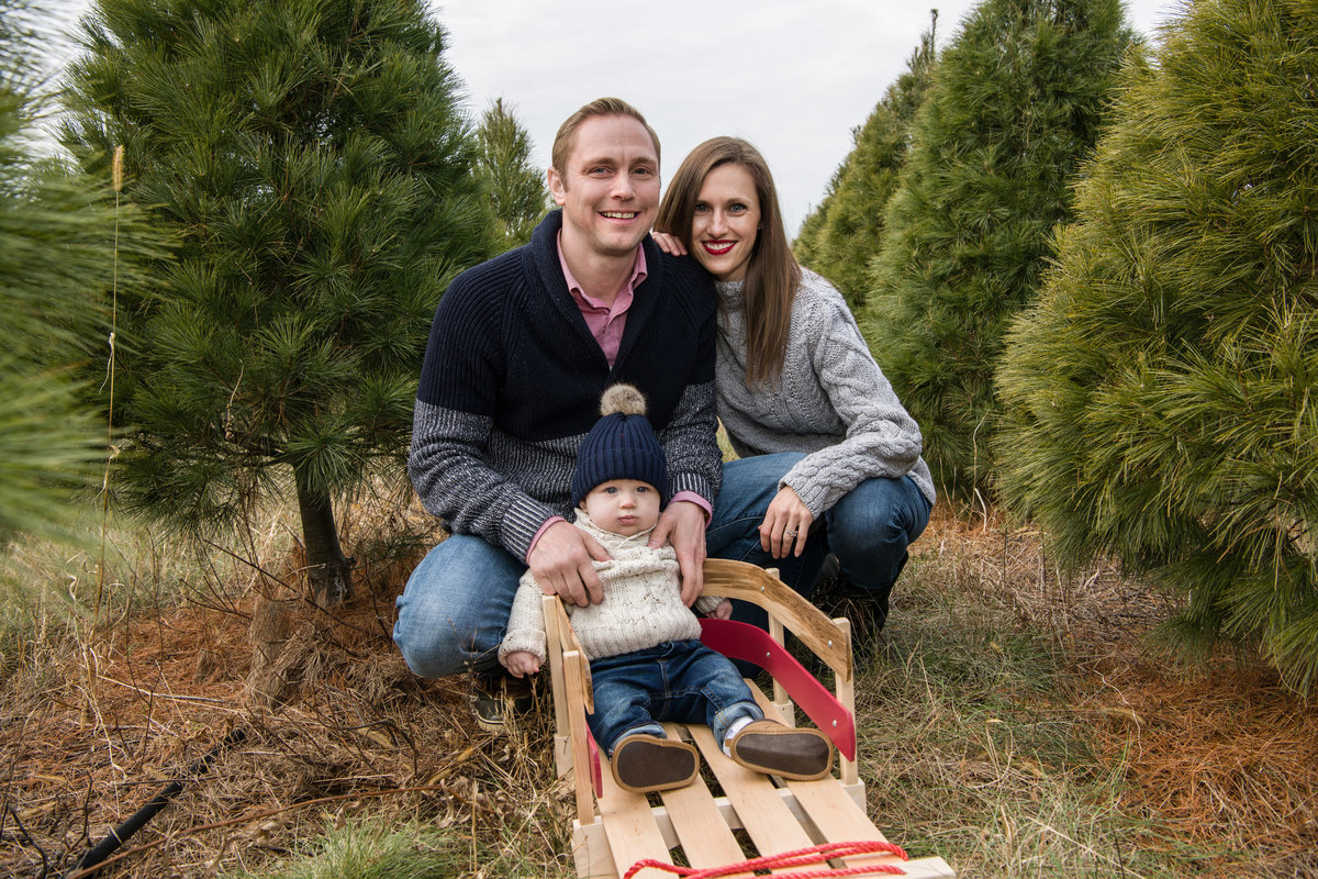 Mom, dad and baby together in pine trees for Christmas photography